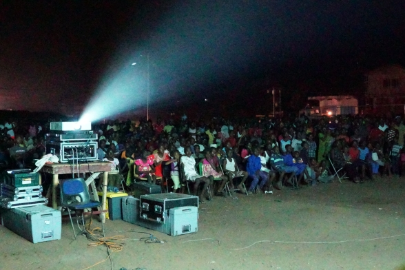 A usually-dark big plaza in Freetown getting packed for public viewing